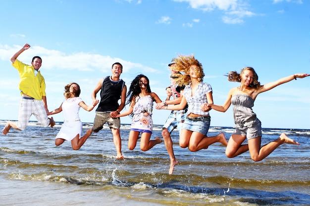 Adolescenti felici che giocano al mare Foto Gratuite