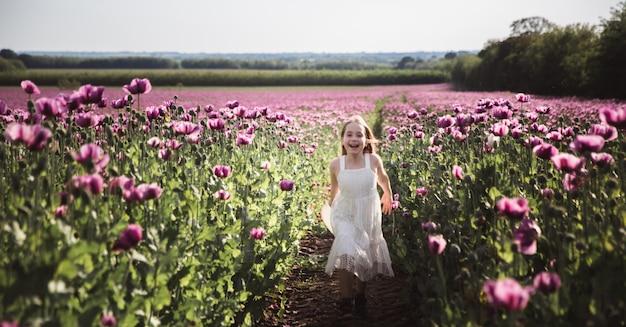 Adorabile bambina con i capelli lunghi in abito bianco solitario a piedi nel campo lilla poppy flowers Foto Premium