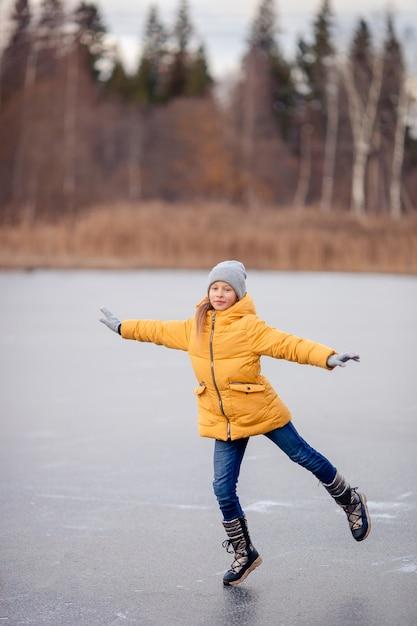 Adorabile bambina pattinaggio sulla pista di pattinaggio Foto Premium
