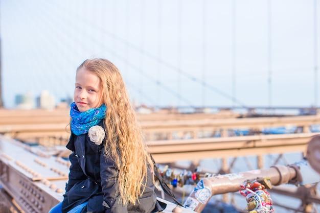 Adorabile bambino al ponte di brooklyn a new york city con vista sulla strada Foto Premium
