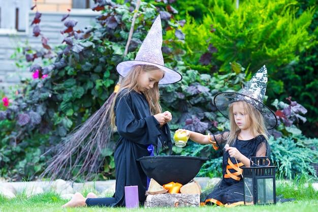 Adorabili bambine in costume da strega ad halloween si divertono Foto Premium