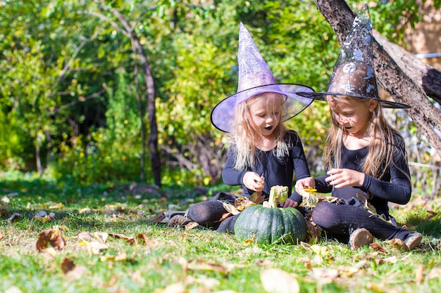 Adorabili bambine in costume da strega che lanciano un incantesimo su halloween Foto Premium