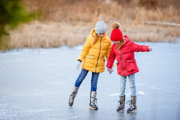 Adorabili bambine pattinaggio sulla pista di pattinaggio Foto Premium