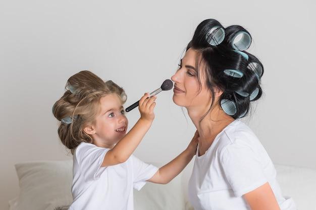 Adoro mia mamma. felice festa della mamma. bella madre con la sua piccola figlia carina si divertono a casa. truccarsi e sorridere. Foto Premium