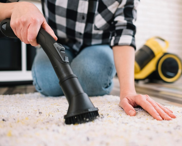 Adulto che aspira il tappeto Foto Gratuite