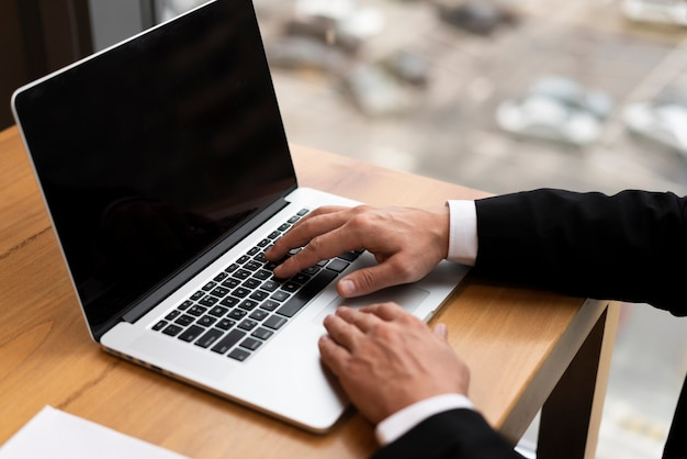 Adulto del primo piano che lavora il suo computer portatile all'ufficio Foto Gratuite