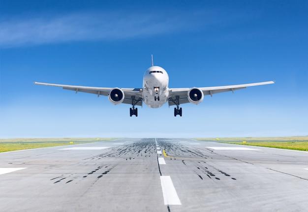 Aeroplano di atterraggio esattamente sull'aeroporto della pista Foto Premium