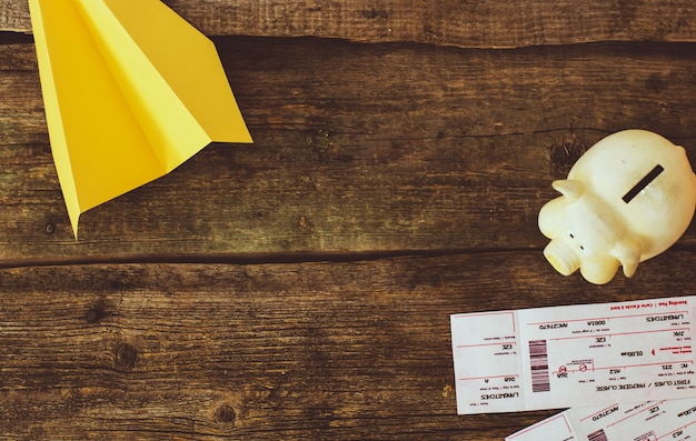 Aeroplano di carta e del porcellino salvadanaio su fondo di legno Foto Gratuite