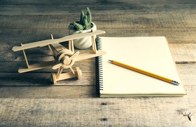 Aeroplano di legno del giocattolo con il taccuino in bianco e matita sulla tavola di legno Foto Premium