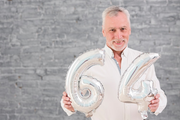 Aerostato felice della stagnola d'argento della tenuta dell'uomo senior sul suo 64 compleanno Foto Gratuite