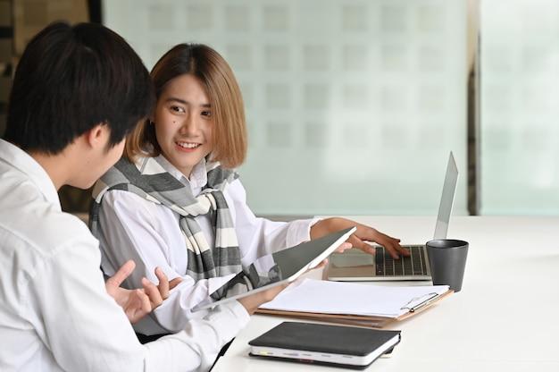 Affare che incontra insieme la compressa digitale in ufficio moderno Foto Premium