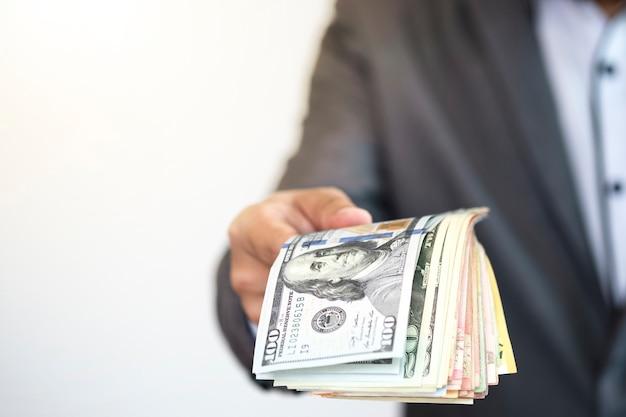 Affare del gestore di fondi che tiene la banconota del dollaro americano e che dà a qualcuno Foto Premium