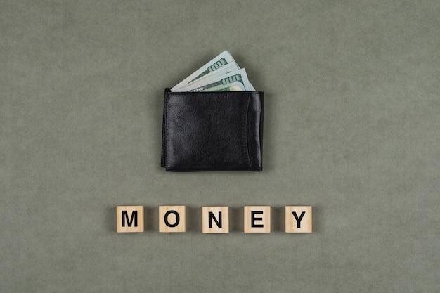 Affare e concetto finanziario con soldi in portafoglio, cubi di legno sulla disposizione del piano della superficie di gray. Foto Gratuite