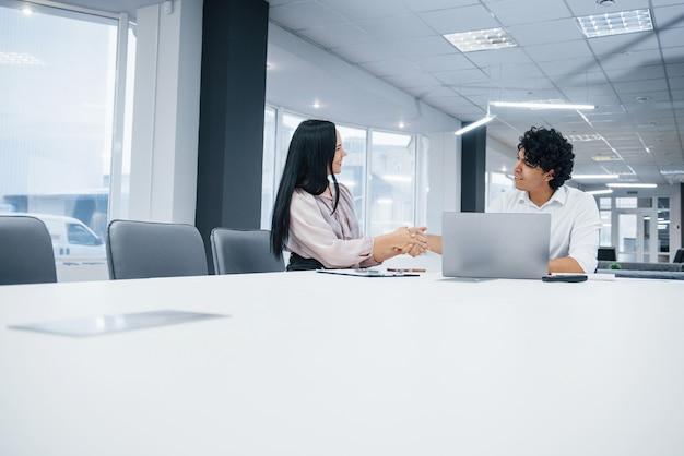 Affare riuscito tra due persone che siedono vicino al tavolo e al computer portatile su di esso nell'ufficio bianco Foto Premium