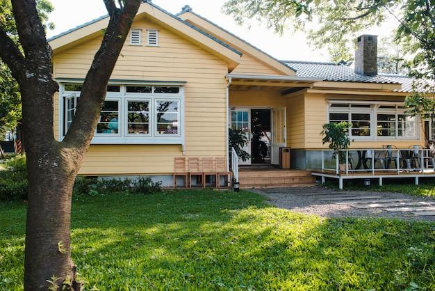 Affascinante casa gialla con finestre in legno e giardino erboso verde Foto Gratuite