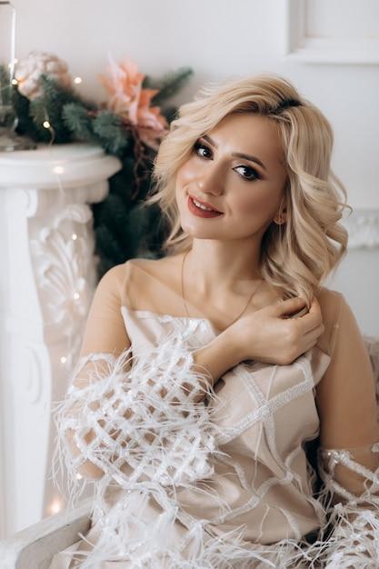 Affascinante donna bionda in abito bianco si pone in una stanza con grande albero di natale Foto Gratuite