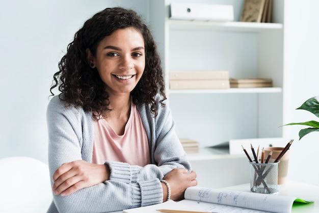 Affascinante giovane donna seduta sul posto di lavoro Foto Gratuite