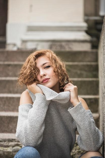 Affascinante signora sorridente che tiene il colletto del maglione e seduto sui gradini Foto Gratuite