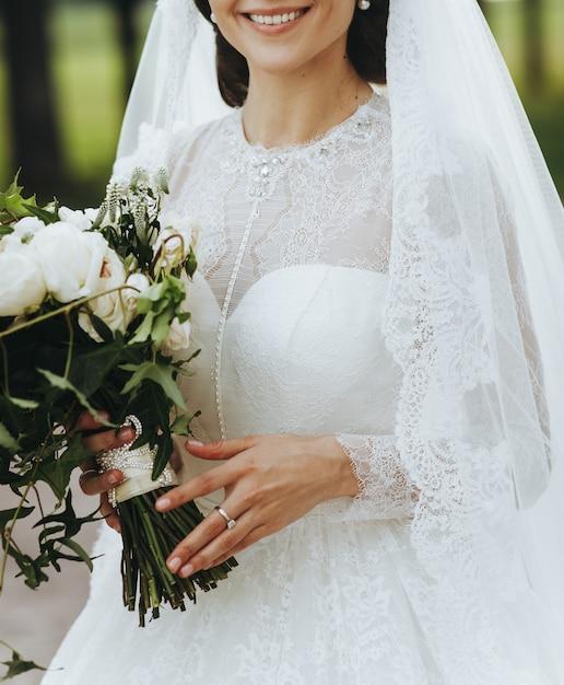 Affascinante sposa con bouquet di classe si trova al di fuori Foto Gratuite
