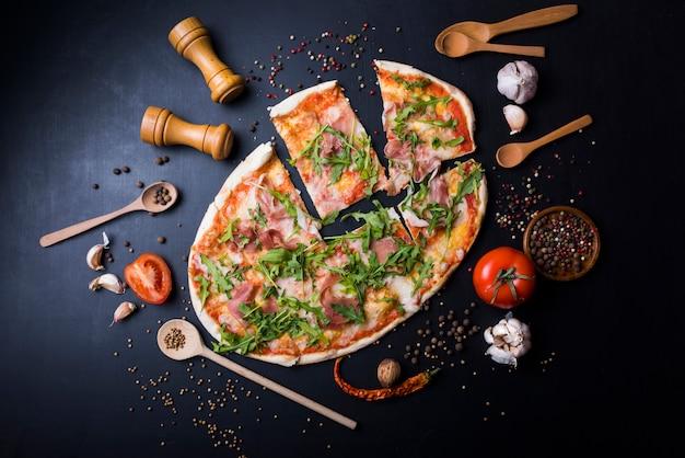 Affetta la pizza italiana con utensili e ingredienti sopra il piano di lavoro nero della cucina Foto Gratuite