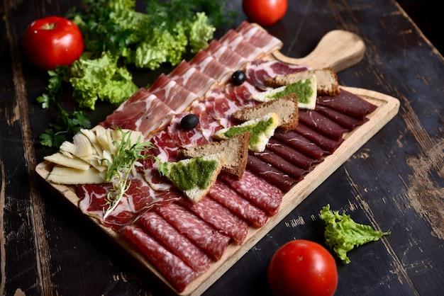 Affettare salsiccia e carne con crostini e olive su una tavola di legno Foto Premium