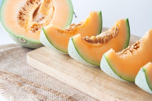 Affettato melone giapponese fresco, melone arancione sul tagliere. messa a fuoco selettiva Foto Premium