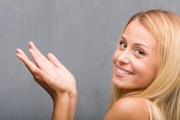 Affronti il primo piano, ritratto di giovane donna bionda naturale che tiene qualcosa con le mani Foto Premium