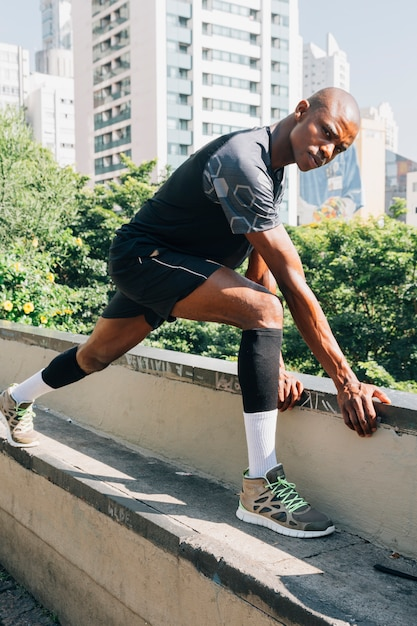 African maschio corridore atletico stretching muscoli sul tetto Foto Gratuite