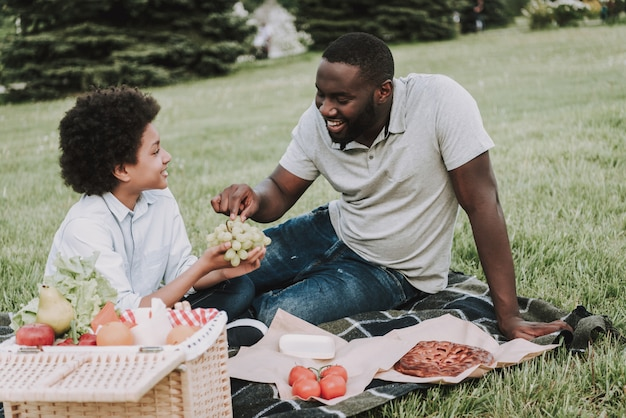 Afro boy contiene uva e padre afro si estende per provare. Foto Premium