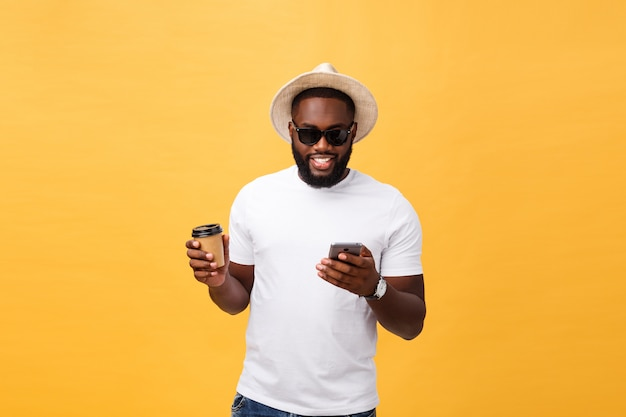 Afroamericano bello con il telefono cellulare e porta via la tazza di caffè. Foto Premium
