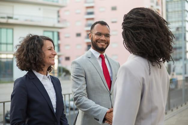 Agente che incontra i clienti vicino all'edificio per uffici Foto Gratuite