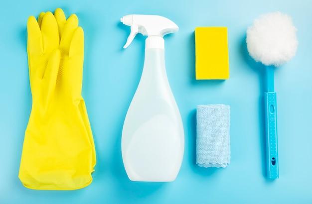 Agente detergente e prodotti per la pulizia, spugne, tovaglioli e guanti di gomma, sfondo blu. vista dall'alto Foto Premium