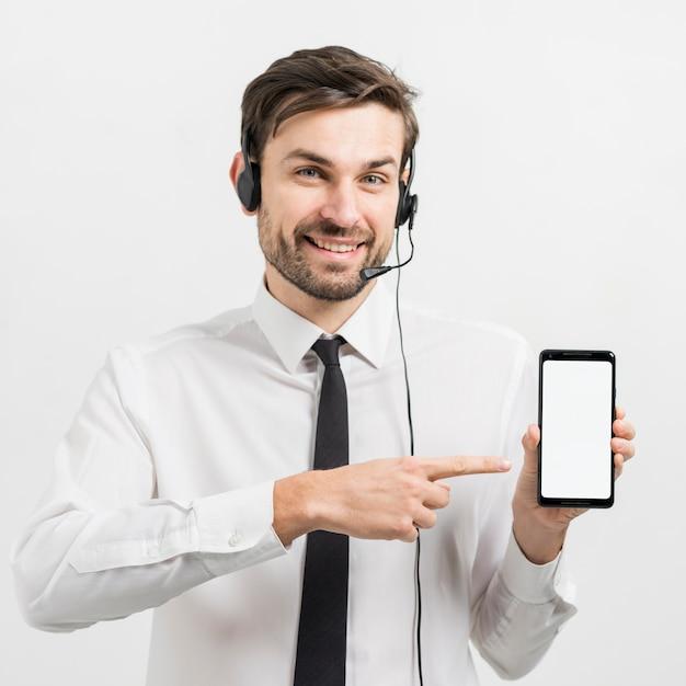 Agente di call center che presenta il modello di smartphone Foto Gratuite