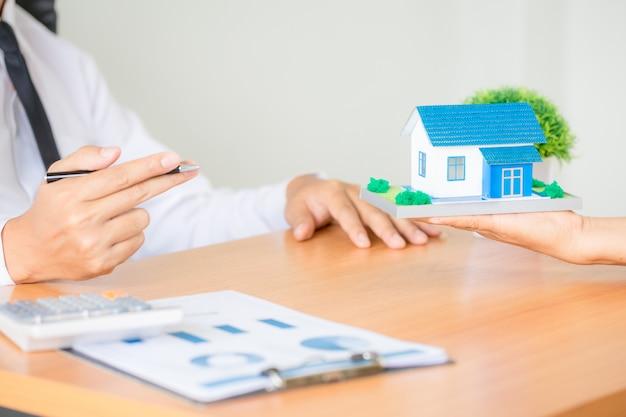 Agente di intermediazione immobiliare che presenta e consulta al cliente l'accordo sul modulo di assicurazione del segno decisionale Foto Gratuite