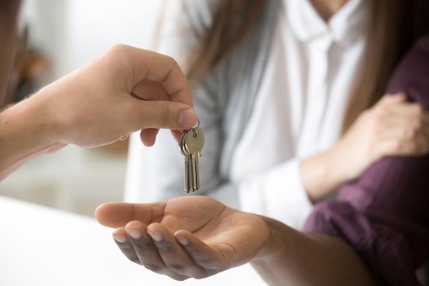 Agente immobiliare che fornisce le chiavi africane del cliente, coppia che compra nuova casa, primo piano Foto Gratuite