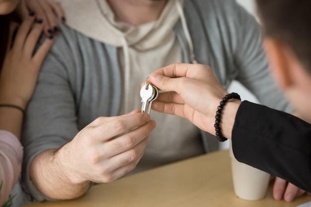 Agente immobiliare che fornisce le chiavi delle coppie, compranti il concetto della nuova casa, fine su Foto Gratuite