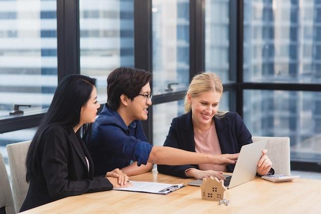 Agente immobiliare che incontra la coppia asiatica per offrire proprietà della casa, assicurazione sulla vita e investimento della casa Foto Premium