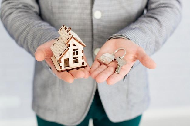 Agente immobiliare con casa figurine e chiave Foto Gratuite