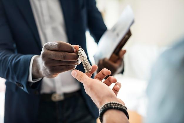 Agente immobiliare consegnando la chiave di casa a un cliente Foto Gratuite