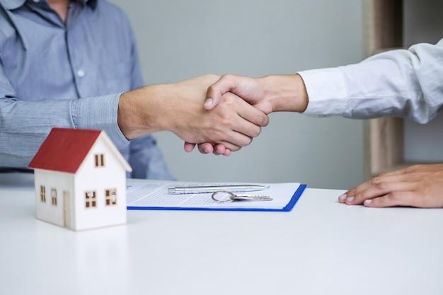 Agente immobiliare e clienti che si stringono la mano insieme celebrando il contratto finito Foto Premium
