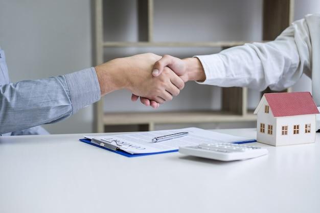 Agente immobiliare e clienti che stringono le mani insieme celebrando il contratto finito dopo la firma Foto Premium