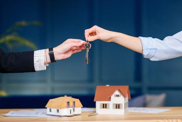 Agente immobiliare femminile che fornisce la chiave dal nuovo appartamento, casa ai clienti femminili. Foto Premium