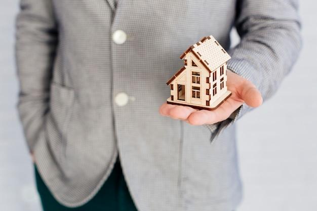 Agente immobiliare irriconoscibile che tiene la figurina della casa Foto Gratuite