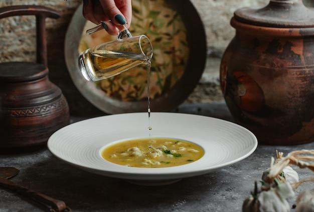 Aggiunta di olio d'oliva alla zuppa di brodo di pollo. Foto Gratuite