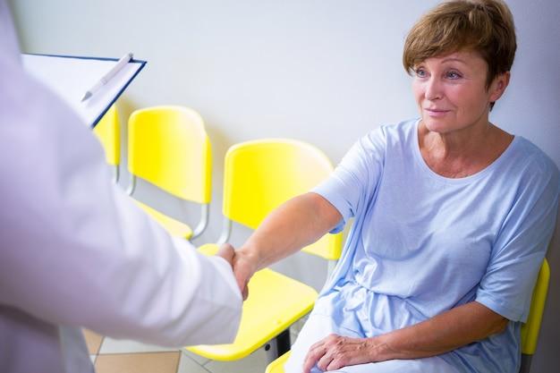 Aggiusti la stretta di mano con il paziente nella sala di attesa Foto Premium