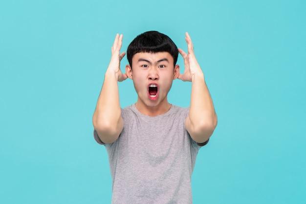 Aggressivo giovane arrabbiato uomo asiatico che grida Foto Premium