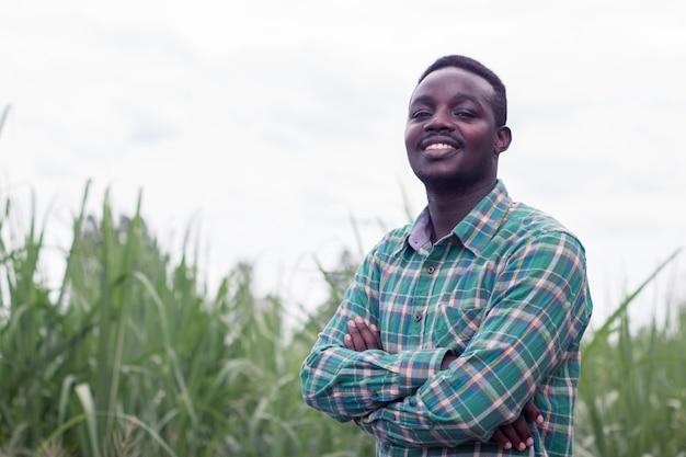 Agricoltore africano con il supporto del cappello nell'azienda agricola verde Foto Premium
