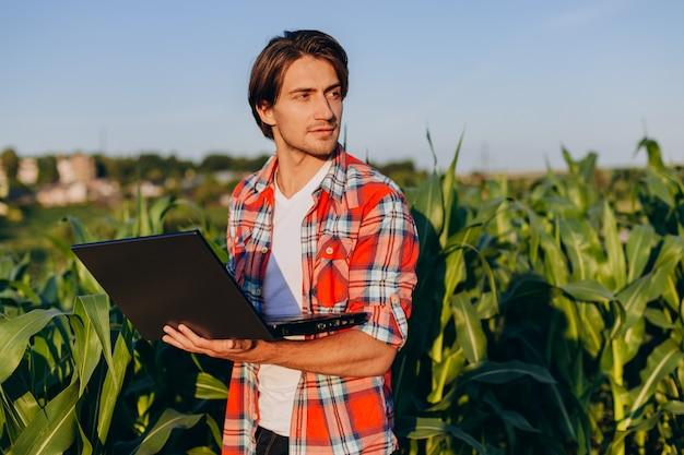 Agronomo che sta in un campo che tiene computer portatile aperto e che sorride e che guarda fuori Foto Premium