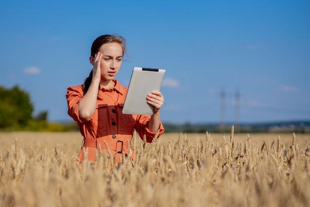 Agronomo di donna indoeuropeo tecnologo con computer tablet nel campo del grano controllo qualità Foto Premium