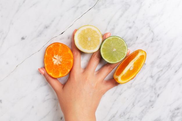 Agrumi. arancia, limone, pompelmo, mandarino e lime su una pietra alla moda Foto Premium